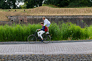 In Naarden fietst een jongen met een vriend staand achterop de bagagedrager van de fiets.<br /> <br /> In Naarden-Vesting a boy is cycling with a friend standing on the carrier.