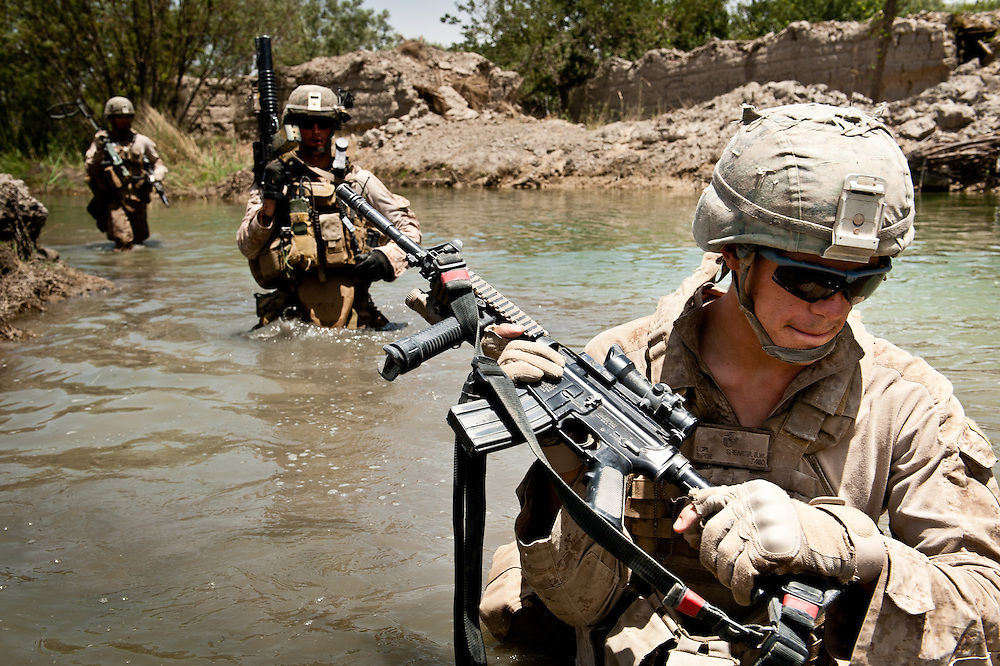 Lance Corporal Brian Shearer, 20, from Rapid City, South Dakota, wades through an irrigation canal, looking for the body of an insurgent suspected to have been killed during a firefight.