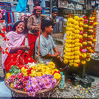 Friends laugh together as they tend a flower stall in the streets of Kathmandu, Nepal.