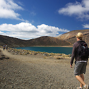 Walkers pass the Blue Lake on the Tangariro Alpine Crossing.  The Tongariro Alpine Crossing is a 7-8 hour hike traversing two active volcanoes within the Tongariro National Park, North Island, New Zealand.  It is considered to be the best one day hike in New Zealand and in the top 10 one day hikes in the world. Packed into the 19.4km hike is an array of diverse landscapes and vegetations. From tussock like alpine meadows, to rugged lava flows, desert like craters and emerald lakes.  The Tongariro Alpine  9th January 2011. Photo Tim Clayton..