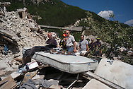Inhabitans escorted by firemen are guided to the remains of their houses to retrive their goods in Pescara del Tronto