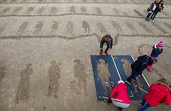 © Licensed to London News Pictures. 11/11/2018. Folkestone, UK. Stencils are used to make sand images of WW1 soldiers and nurses on the beach at Folkestone, Kent during an Armistice Centenary event entitled 'Pages of the Sea'. Portraits are being created by communities on 32 beaches around the UK to say goodbye and thank you, to the millions of men and women who left these shores during the war, many never to return. Lieutenant Wilfred Edward Salter Owen, MC died on 4th November 1918 only days before the Armistice. One of Britain's most celebrated war poets - his short career was directly inspired by the conflict – he composed nearly all his works from August 1917 to September 1918, many published posthumously. Photo credit: Peter Macdiarmid/LNP