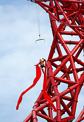 © Licensed to London News Pictures . 05/04/2014. London, UK.  Aerial performance by acrobats from Aircraft Circus abseil the ArcelorMittal Orbit at the Queen Elizabeth Olympic Park. The tower and park open for visitors today (05/04/2014) Photo credit: LNP