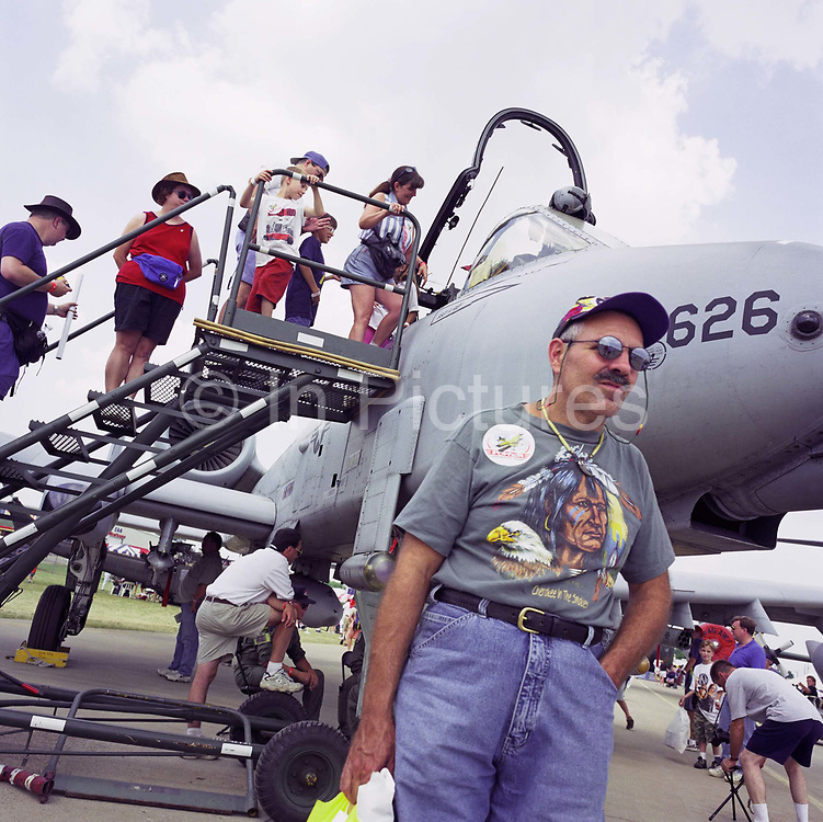 A visitor to Oshkosh Air Venture, the world's largest air show in Wisconsin USA, stands by an A-10 Thunderbolt Tank Buster or Warthog. Wearing a t-shirt depicting a Cherokee Indian and a Bald Eagle, the tourist awaits family as aviation enthusiasts climb steps to the aircraft's cockpit. The Fairchild-Republic A-10 Thunderbolt II is a single-seat, twin-engine jet aircraft designed to provide close air support of ground forces by attacking tanks, armoured vehicles, and other ground targets. It has also been involved with British friendly fire incidents in Iraq. Close to a million populate the mass fly-in over the week, a pilgrimage worshipping all aspects of flight. Picture from the 'Plane Pictures' project, a celebration of aviation aesthetics and flying culture, 100 years after the Wright brothers first 12 seconds/120 feet powered flight at Kitty Hawk,1903.