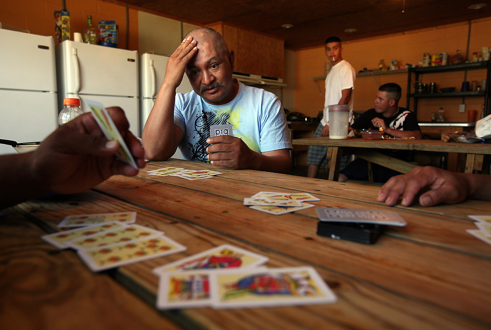 Martin Ortega, of San Luis, Mexico plays cards with house mates. Ortega is married with four kids, he has worked at Titan Farms for eight years.
