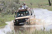 Africa, Tanzania, Serengeti National Park, Safari tourists in an open top Jeep crossing a water barrier