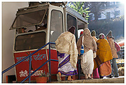 Ladies wearing traditional sari's enter a small cable car from Joshimath en-route to Auli ski resort in the state of Uttarakhand in Northern India