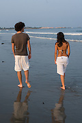 A couple takes an evening stroll on a beach in Narragansett, Rhode Island.