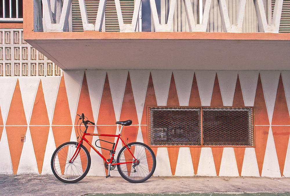 Dusky orange, Miami Modern (MiMo) design on a small Miami Beach apartment building on Ocean Drive, with a red bicycle leaning against the patterned wall
