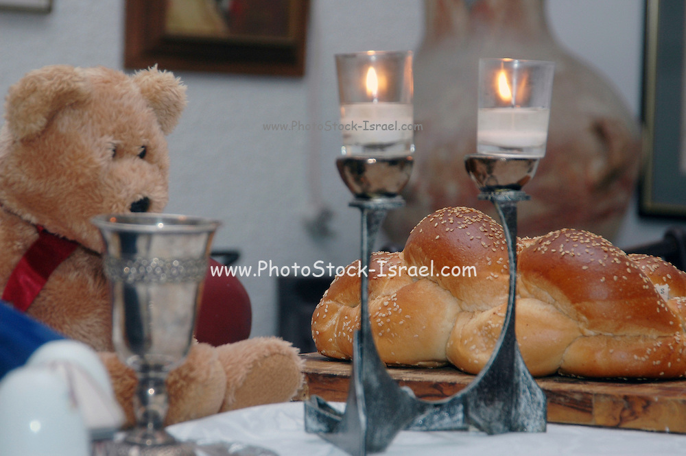 A teddy bear at the Jewish Shabat table with candles, wine and chala