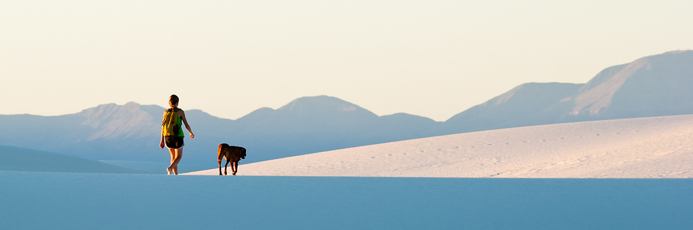 A woman and her dog walk the dunes at White Sands National Monument in New Mexico.
