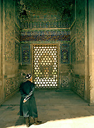 An Uzbek admiring mosaic of the Ulughbek Medressa, while on pilgrimage at the Registan, Samarkand's most famous building and a symbol of Central Asia's architecture. The fabled city of Samarkand, on the ancient Silk Road. Uzbekistan.