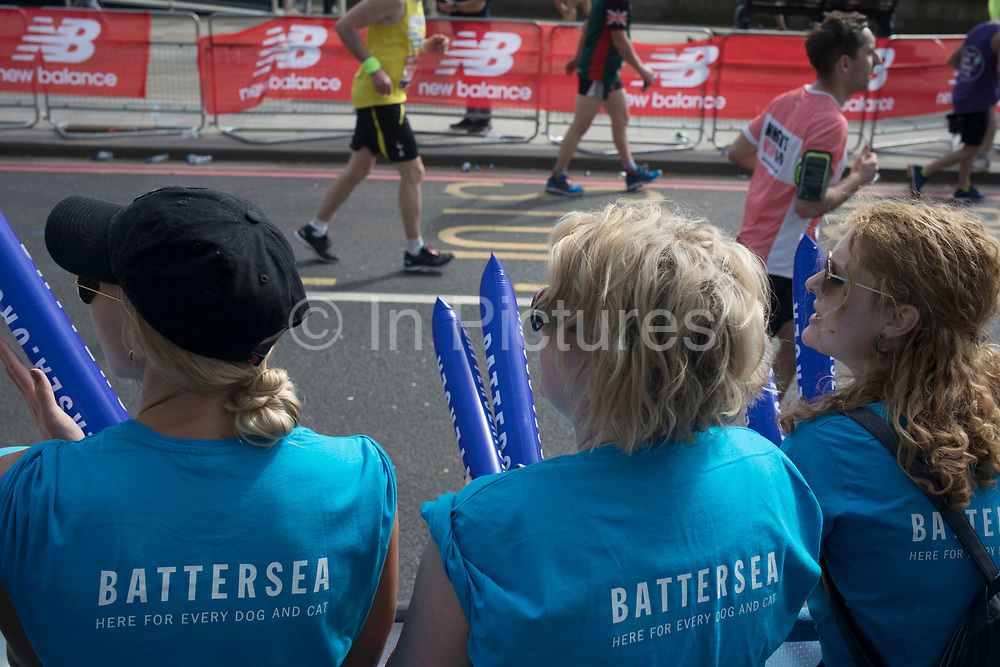 Charity supporters from Battersea Dogs Home encourage participants taking part in the London Marathon on 22nd April 2018 in London, England, United Kingdom. The London Marathon, presently known through sponsorship as the Virgin Money London Marathon, is a long-distance running event. The event was first run in 1981 and has been held in the spring of every year since. The race is mainly known for ebing a public race where ordinary people can challenge themsleves while raising great amounts of money for various charities.