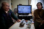 Onagawa  Bonze Yamato Bijo -  logements provisoires Kasetsu jutaku  Mars 2012.Le bonze YAMATO Bijo est volontaire. Il rend visite aux personnes et parle longuement avec elles. Le culte nest pas sa priorité même si le réconfort par la prière est important en cette période de commémoration. En arrière plan, le premier téléfilm tourné sur les lieux de la catastrophe est diffusé sur NHK.