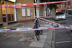© Licensed to London News Pictures. 01/07/2019. London, UK. Blood and a broken bottle are seen on the pavement as a man is fighting for his life in hospital having sustained puncture injuries to the neck by what appeared to a a broken wine bottle. The victim in his 30s is understood to be in a critical condition following the assault. Police responded to a call at 5.12pm reporting a fight and attended an address in Argyle Road, West Ealing. Another man also in his 30s has been arrested.Photo credit: Guilhem Baker/LNP