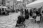 Many outdoor cafes and restaurants line the main streets of Matera, Italy.