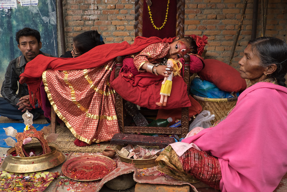 The Bungamati Kumari, a pre-pubescent girl and living goddess, with entourage take part in a ceremony in Bungamati in the Kathmandu Valley, Nepal, just moments before the major earthquake of 25 April 2015 struck. She never left the site during the tremors and, luckily, the wall behind her did not fall. She is resting, lying down on her throne with a doll in her hand. Offerings of money lie in a bowl beneath her.