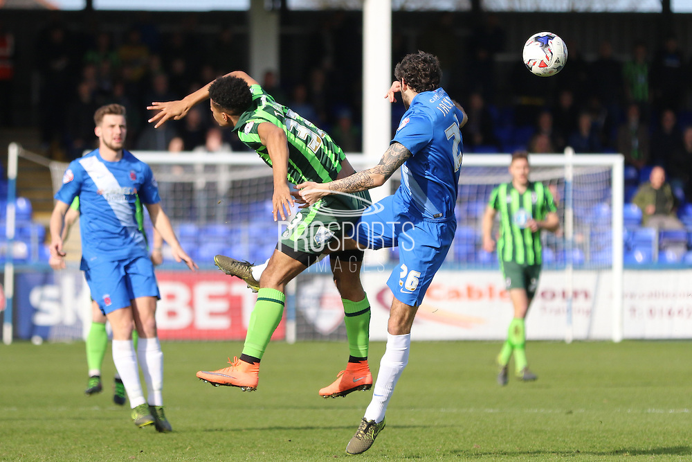 Lyle Taylor forward for AFC Wimbledon (33) and Hartlepool United defender Adam Jackson (26) tussle during the Sky Bet League 2 match between Hartlepool United and AFC Wimbledon at Victoria Park, Hartlepool, England on 25 March 2016. Photo by Stuart Butcher.