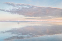 Sailboat and morning clouds refelected in calm waters of Bellingam Bay   Washington