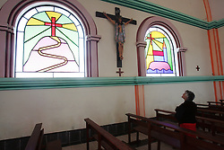 """A woman prays  at at church that Father Sebastian Obermaier built in El Alto, Bolivia. a town he has lived in for 27 years .  """"I don't feel Bolivian, I feel Aymara"""" he says, referring to the Aymara indigenous population that makes up more than 80% of El Alto. Father Obermaier has been designing and building churches in El Alto for the past 10 years, with a goal of building one church for every 10,000 inhabitants of the city, which currently has nearly 700,000 people living in it.  Everyone that visits Bolivia can see his numerous churches from the window of their airplane as it lands in El Alto.  The churches are marked by a style unique to Father Obermaier, that mixes indigenous symbols with tall towers and bright colors, that leave every church looking different, as if they were straight out of a children's pop-up book."""