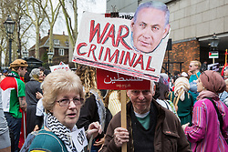 London, UK. 30th March, 2019. A man holds a sign showing an image of Israeli Prime Minister Benjamin Netanyahu and the text 'war criminal' at a Rally for Palestine outside the Israeli embassy to demand freedom, justice and equality for the Palestinian people. The rally was organised by Palestine Solidarity Campaign, Stop the War Coalition, Palestinian Forum in Britain, Friends of Al- Aqsa and Muslim Association of Britain.
