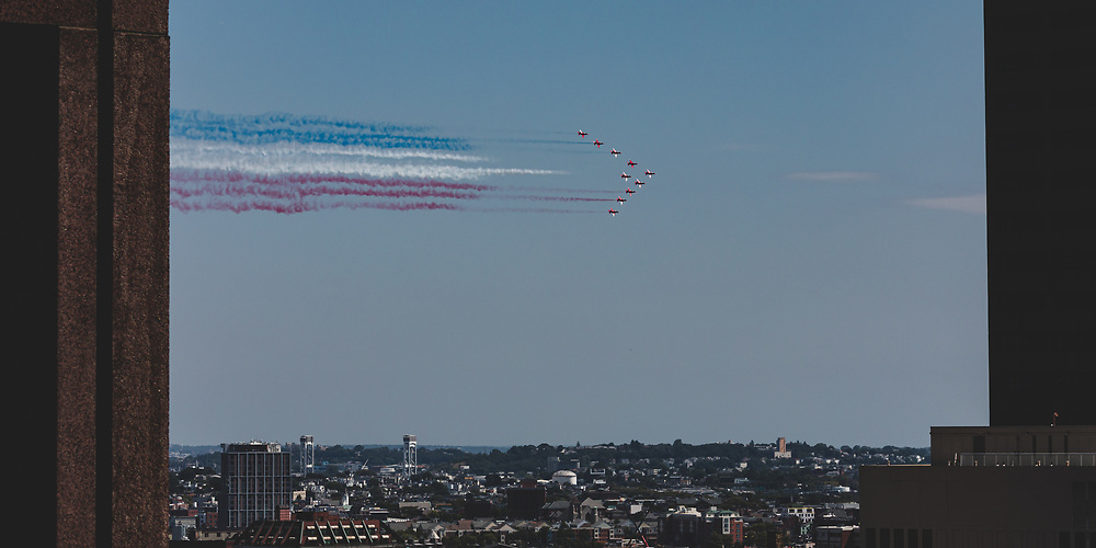 The British Royal Air Force Red Arrows performing a flyby of Boston on a summer morning.