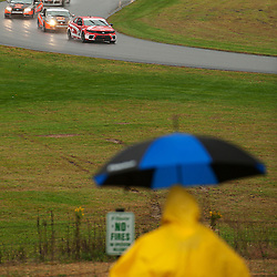 A young fan avoids the rain while watching a pack lead by The Kinetic/Kia Racing Kia Forte Koup driven by Mike Galati and Mark Wilkins during the Grand-Am Continental Tire Sports Car Challenge ST race at Lime Rock Park in Lakeville, Conn.