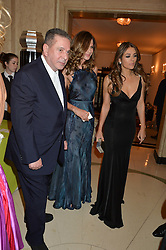 Left to right, CHARLES SAATCHI, TRINNY WOODALL and ELIZABETH HURLEY at the QBF Spring Gala in aid of the Red Cross War Memorial Children's Hospital hosted by Heather Kerzner and Jeanette Calliva at Claridge's, Brook Street, London on 12th May 2015.