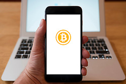 Using iPhone smartphone to display logo of Bitcoin digital currency