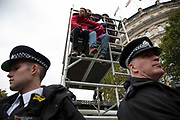 Extinction Rebellion disruption begins as the activists take a high position on a tower and block 12 sites around Westminster on 7th October 2019 in London, England, United Kingdom. Extinction Rebellion is a climate change group started in 2018 and has gained a huge following of people committed to peaceful protests. These protests are highlighting that the government is not doing enough to avoid catastrophic climate change and to demand the government take radical action to save the planet.