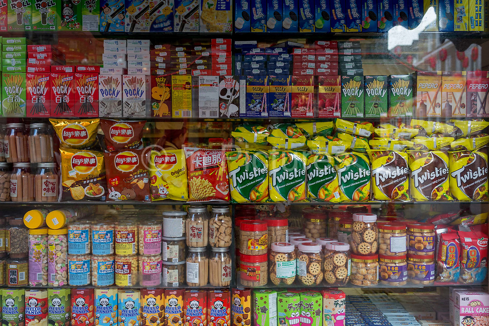 A detail of assorted snacks including biscuits, crisps and other merchandise on shelves in a corner shop convenience store window on Gerrard Street, Chinatown, on 5th March 2018, in London, England.