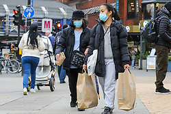 © Licensed to London News Pictures. 01/11/2020. London, UK. A woman wearing face covering with Primark shopping bags in north London, as panic buying continues. This is following the announcement of the second lockdown in England from Thursday 5 November until Wednesday 2 December,  as coronavirus cases are increasing. Non-essential shops such as Primark will close of Thursday. Minister for the Cabinet Office, Michael Gove, has said that the four-week shut-down could be extended into December if needed. Photo credit: Dinendra Haria/LNP