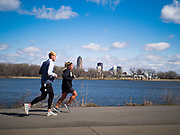 """29 MARCH 2020 - DES MOINES, IOWA: Joggers on an empty running trail around Gray's Lake, a popular park and lake near downtown Des Moines, with the city skyline in the background, Sunday. On Sunday morning, 29 March, Iowa reported 336 confirmed cases of the Novel Coronavirus (SARS-CoV-2) and COVID-19. There have been four deaths attributed to COVID-19 in Iowa. Restaurants, bars, movie theaters, places that draw crowds are closed until 07 April. The Governor has not ordered """"shelter in place""""  but several Mayors, including the Mayor of Des Moines, have asked residents to stay in their homes for all but the essential needs. People are being encouraged to practice """"social distancing"""" and many businesses are requiring or encouraging employees to telecommute.        PHOTO BY JACK KURTZ"""