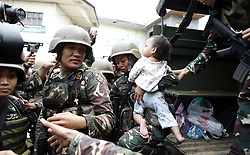 June 25, 2017- Marawi, Philippines - A soldier carries a baby who was rescued from Marawi, Philippines. Five civilians, who had been trapped in Marawi with rebels, were rescued by government negotiators during a 8-hour truce declared by the government. (Credit Image: © Jeoffrey Maitem/Xinhua via ZUMA Wire)