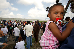 29 August 2006. New Orleans, Louisiana. Lower 9th ward. <br /> Returning home a year later and carrying his grand daughter Germain Saras (17mths), Charles Duplessis  meets old friends and neighbours who gather close to the levee wall. Civilians gathered at the site of the breach of the industrial canal for the Great Flood commemoration and memorial ceremony to 'honor and remember our loved ones who have passed.' People came to mark the anniversary of devastating hurricane Katrina at the site where the now repaired and allegedly in theory stronger levee flood wall. The levee breached along the industrial canal at the point where people gathered, needlessly killing hundreds of innocent civilians in the worst engineering disaster in US history.<br /> Photo Credit©; Charlie Varley/varleypix.com
