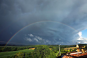 dark clouds and blue sky with rainbow