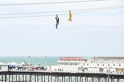 © Licensed to London News Pictures. 17/06/2018. Brighton, UK. Members of the public take a ride on the Brighton Zip Wire attraction on the Brighton and Hove seafront. Photo credit: Hugo Michiels/LNP
