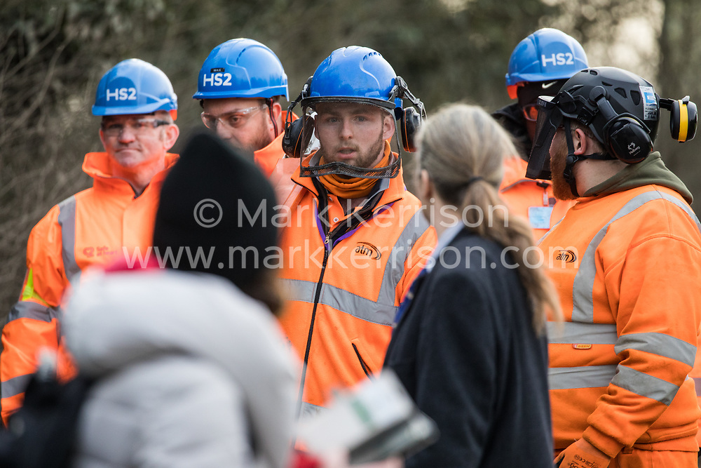 Harefield, UK. 8 February, 2020. Environmental activists monitor HS2 engineers with a chainsaw on Harvil Road in the Colne Valley. HS2 had scheduled tree felling work in the area for the high-speed rail project, implementing road and rail closures for this purpose, but were prevented from any tree felling by action from the environmental activists.