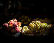 Mercado de Nuestra Señora de África, Grape and Dragon Fruit in exposition at the market. The light filtering by the archs draw a still life as in a barroque painting.