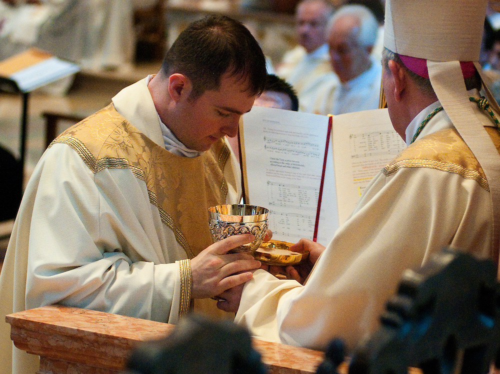 The archbishop presents Erich Wiess with bread and wine as a sign of presiding at the Eucharist.