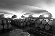 The old style vaulted barrel aging cellar with barriques pieces with maturing wine black and white bw, Maison Louis Jadot, Beaune Côte Cote d Or Bourgogne Burgundy Burgundian France French Europe European