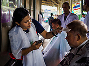 12 SEPTEMBER 2018 - BANGKOK, THAILAND: A barber checks her work on a traveler at Hua Lamphong train station in Bangkok. Barber schools set up in the station and offer free haircuts to travelers.    PHOTO BY JACK KURTZ