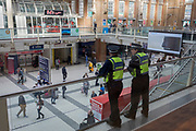 Special constables (PCSOs) watch over concourse passengers at Liverpool Street mainline Station, on 17th April 2018, in the City of London, England.