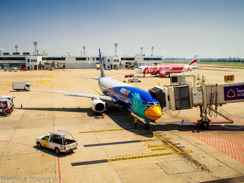 02 APRIL 2015 - BANGKOK, THAILAND:   A NOK AIrlines and Air Asia aircraft on aprons at Don Mueang Airport in Bangkok. The International Civil Aviation Organization (ICAO), a United Nations agency, issued a report critical of record keeping and maintenance reports for Thailand's civil aviation industry, including most Thai air carriers. The ICAO report allegedly showed that the Thai Department of Civial Aviation (DCA) was able to meet only 21 out of 100 ICAO requisites. Several Asian countries, including South Korea, Japan and China have imposed limits of Thai registered aircraft since the release of the ICAO report and the European Union has begun to review the safety records of Thai Airways International (THAI) aircraft that fly to Europe.   PHOTO BY JACK KURTZ