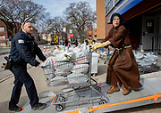 Chicago police Officer Jeffrey Dohnal helps Sister Stephanie Baliga move bags of food Tuesday, March 24, 2020 at Mission of Our Lady of the Angels in Humboldt Park. Chicago police assisted the church in delivering the supplies to senior citizens who couldn't visit the regular food pantry due to the coronavirus pandemic. (Brian Cassella/Chicago Tribune)