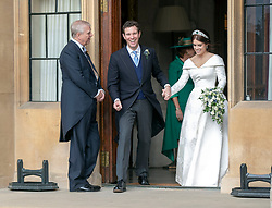 Princess Eugenie and Jack Brooksbank, watched by the Duke of York, leavi Windsor Castle after their wedding for an evening reception at Royal Lodge.