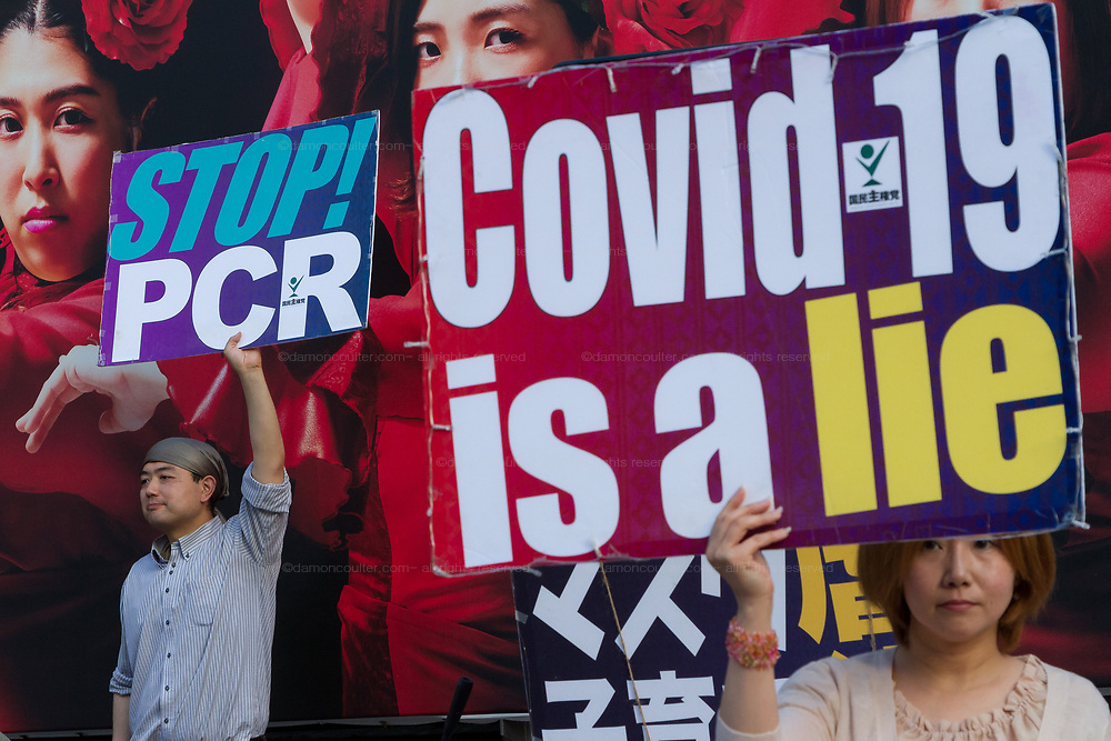 """A Japanese people hold signs saying """"Covid-19 is a lie"""" and """"Stop PCR"""" at a small demonstration against government and societal measures to combat the COVID19 pandemic  Shibuya, Tokyo, Japan. Saturday June 12th 2021. Supporters of Masayuki Hiratsuka of the Popular Sovereignty Party of Japan, who unsuccessfully ran for Tokyo Governor in 2020, held a music festival in the iconic Hachiko Square calling the Coronavirus pandemic a lie."""