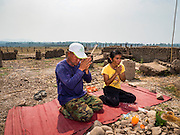 31 MARCH 2016 - NA SAK, LAMPANG, THAILAND: A couple prays in the ruins of an old temple in a village in the Mae Chang Reservoir. The Mae Chang Reservoir in Lampang province was created more than 30 years ago when the Chang River was dammed. Five villages along the river were relocated to hillsides above the river. For the first time since it was flooded, the reservoir is nearly empty and the ruins of the old villages are visible. Many people who remember the old villages are coming down to the ruins to visit them. This part of Thailand hasn't received significant rain in months and many irrigation canals and streams are running dry.    PHOTO BY JACK KURTZ