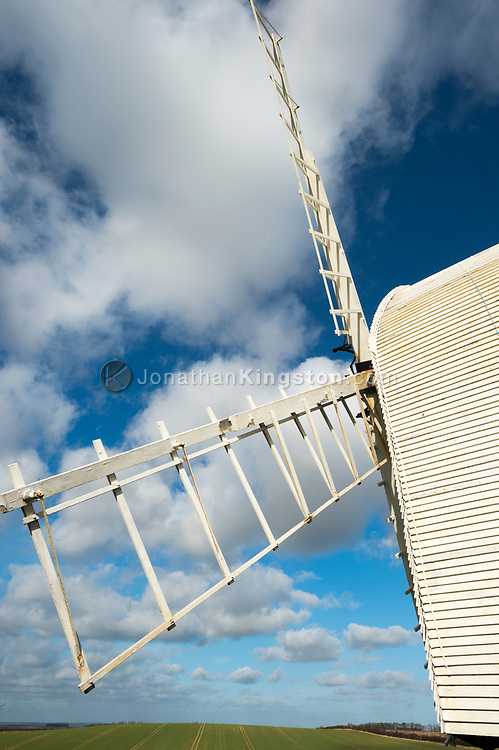 Low angle view of a white windmill, puffy clouds and green fields in Great Chishill, Cambridgeshire, England.
