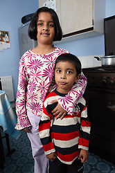 Portrait of brother and sister standing in the kitchen,